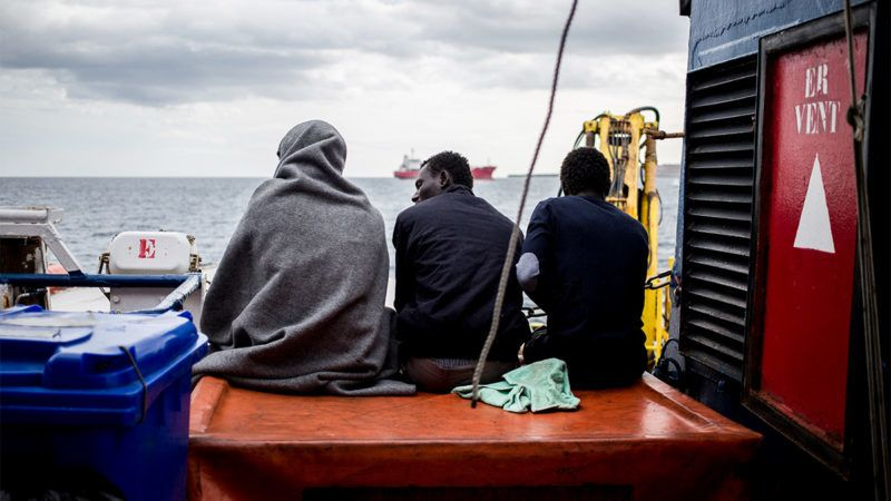 Three of the 47 rescued migrants aboard the Dutch-flagged Sea Watch 3 NGO vessel, sit on the ship's half-deck on January 30, 2019 off Syracuse, Sicily. - 47 rescued migrants aboard the Sea Watch NGO vessel were expected to disembark in Catania after Italy and France, Germany, Malta, Portugal, Romania and Luxembourg agreed to take them in. The fate of the migrants has been at the centre of a standoff between Italy's far-right Deputy Prime Minister Matteo Salvini -- who has closed the ports to migrants and demanded Europe take its share -- and the German NGO Sea Watch. (Photo by FEDERICO SCOPPA / AFP)