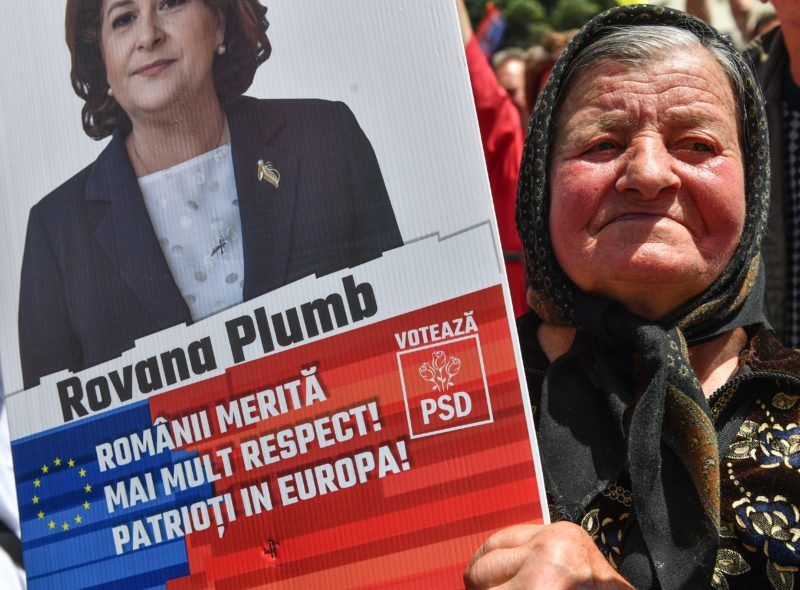 """An elderly woman holds a sign reading """"Romania deserves more respect! Patriots in Europe!"""" advertising Rovana Plumb, the top candidate of the ruling Social Democrate Party (PSD) for Europe during an EU elections rally in Targoviste city on May 19, 2019. - Thousand of people take part in a meeting promoting PSD's EU candidates for the European Parliament scheduled on May 26. (Photo by Daniel MIHAILESCU / AFP)"""