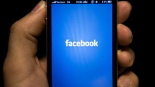 """(FILES) In this file photo taken on May 10, 2012 shows an iPhone displaying the Facebook app's screen in Washington, DC. - Facebook is leaping into the world of cryptocurrency with its own digital money, designed to let people save, send or spend money as easily as firing off text messages.""""Libra"""" -- described as """"a new global currency"""" -- was unveiled June 18, 2019 in a new initiative in payments for the world's biggest social network with the potential to bring crypto-money out of the shadows and into the mainstream. Facebook and an array of partners released a prototype of Libra as an open source code to be used by developers interested in weaving it into apps, services or businesses ahead of a rollout as global digital money next year. (Photo by Brendan SMIALOWSKI / AFP)"""