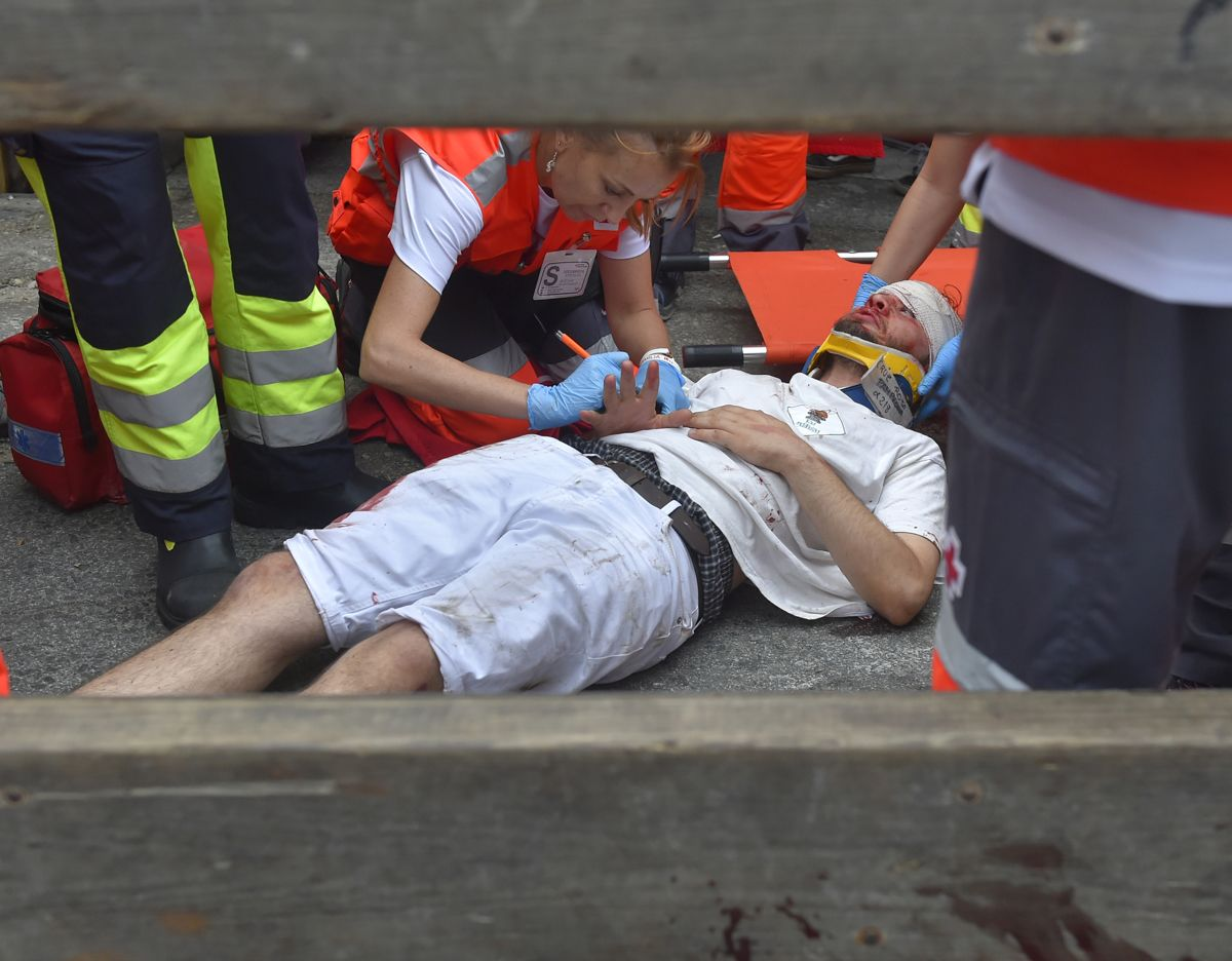 A participant receives medical assistance during the first bullrun of the San Fermin festival in Pamplona, northern Spain on July 7, 2019. - On each day of the festival six bulls are released at 8:00 a.m. (0600 GMT) to run from their corral through the narrow, cobbled streets of the old town over an 850-meter (yard) course. Ahead of them are the runners, who try to stay close to the bulls without falling over or being gored. (Photo by ANDER GILLENEA / AFP)