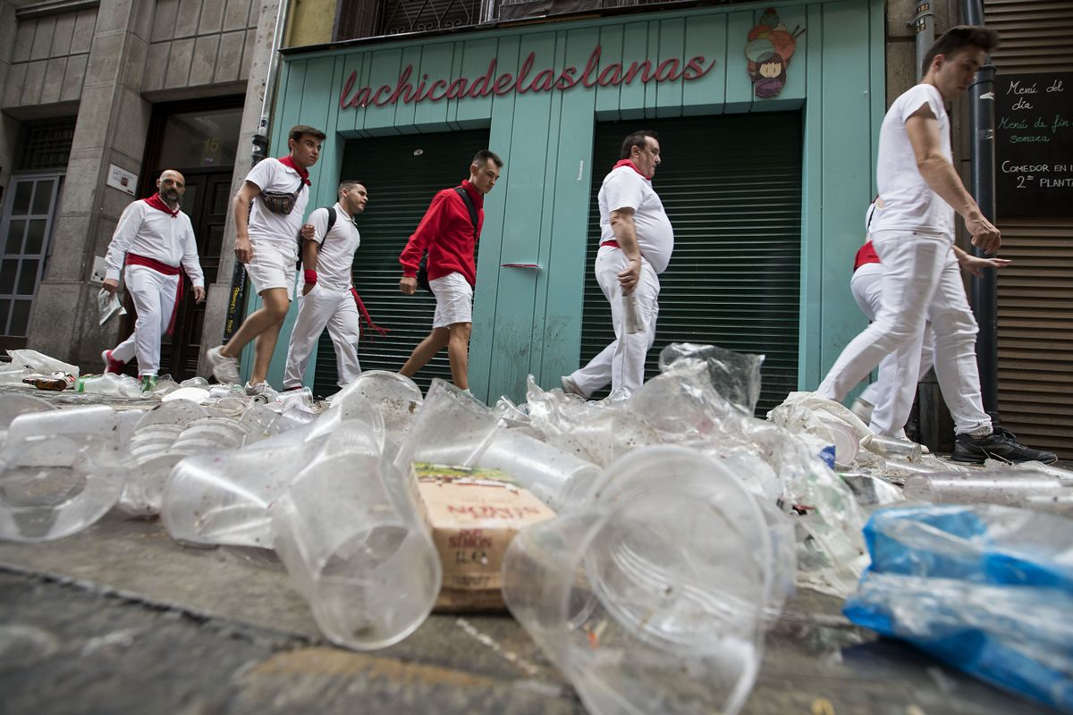 Revellers walk on a dirty street after the first bullrun of the San Fermin festival in Pamplona, northern Spain on July 7, 2019. - On each day of the festival six bulls are released at 8:00 a.m. (0600 GMT) to run from their corral through the narrow, cobbled streets of the old town over an 850-meter (yard) course. Ahead of them are the runners, who try to stay close to the bulls without falling over or being gored. (Photo by JAIME REINA / AFP)