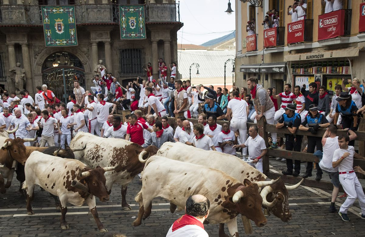 Participants run next to Cebada Gago fighting bulls on the second bullrun of the San Fermin festival in Pamplona, northern Spain on July 8, 2019. - On each day of the festival six bulls are released at 8:00 a.m. (0600 GMT) to run from their corral through the narrow, cobbled streets of the old town over an 850-meter (yard) course. Ahead of them are the runners, who try to stay close to the bulls without falling over or being gored. (Photo by JAIME REINA / AFP)