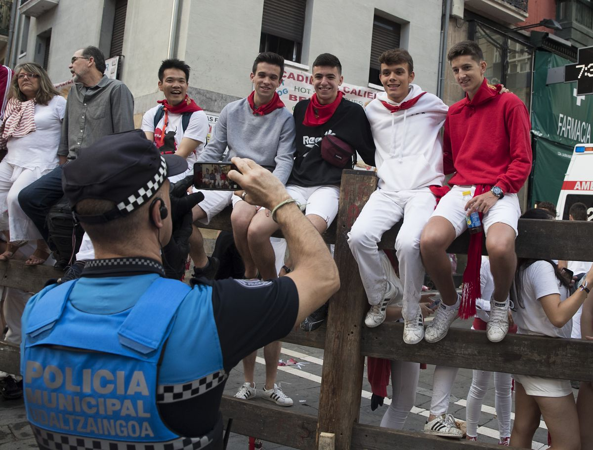 A policeman takes a photo of revellers before the second bullrun of the San Fermin festival in Pamplona, northern Spain on July 8, 2019. - On each day of the festival six bulls are released at 8:00 a.m. (0600 GMT) to run from their corral through the narrow, cobbled streets of the old town over an 850-meter (yard) course. Ahead of them are the runners, who try to stay close to the bulls without falling over or being gored. (Photo by JAIME REINA / AFP)