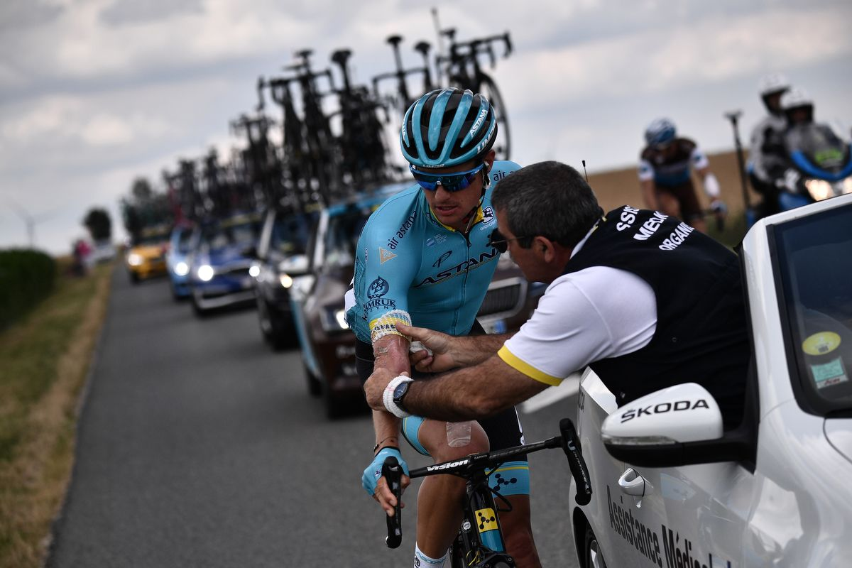 Danish rider Jakob Fuglsang (L) is treated by a medical staff during the third stage of the 106th edition of the Tour de France cycling race between Binche and Epernay, on July 8, 2019. (Photo by Marco Bertorello / AFP)