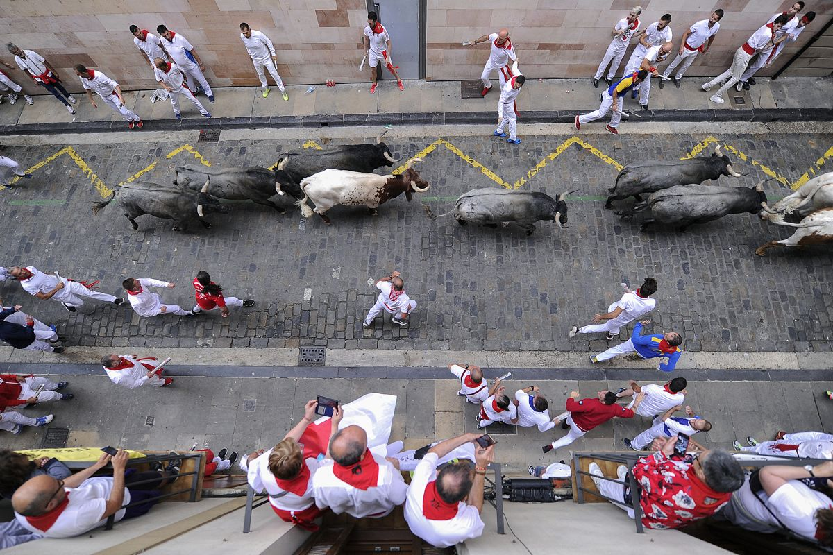 Participants run next to Jose Escolar Gil fighting bulls on the third bullrun of the San Fermin festival in Pamplona, northern Spain, on July 9, 2019. - Each day at 8am hundreds of people race with six bulls, charging along a winding, 848.6-metre (more than half a mile) course through narrow streets to the city's bullring, where the animals are killed in a bullfight or corrida, during this festival dating back to medieval times and also featuring religious processions, folk dancing, concerts and round-the-clock drinking. (Photo by ANDER GILLENEA / AFP)
