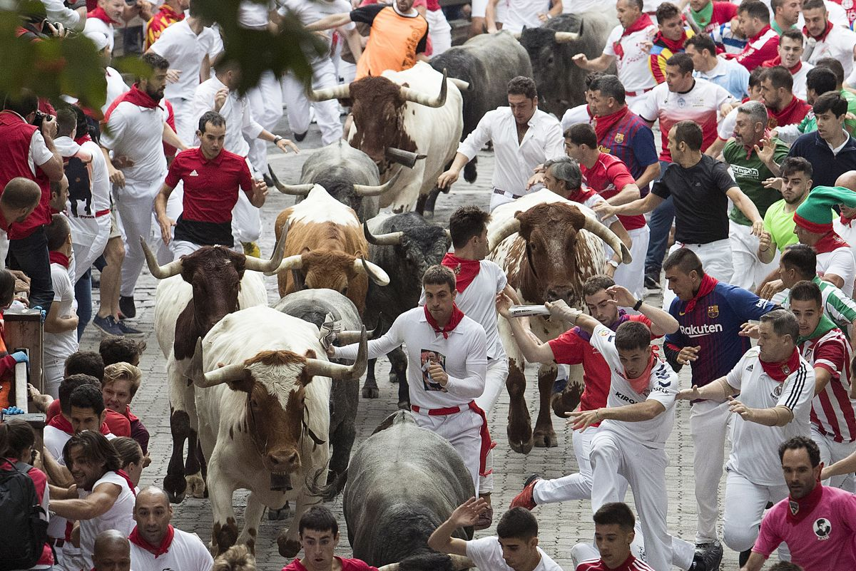 Participants run next to Jose Escolar Gil fighting bulls on the third bullrun of the San Fermin festival in Pamplona, northern Spain, on July 9, 2019. - Each day at 8am hundreds of people race with six bulls, charging along a winding, 848.6-metre (more than half a mile) course through narrow streets to the city's bullring, where the animals are killed in a bullfight or corrida, during this festival dating back to medieval times and also featuring religious processions, folk dancing, concerts and round-the-clock drinking. (Photo by JAIME REINA / AFP)