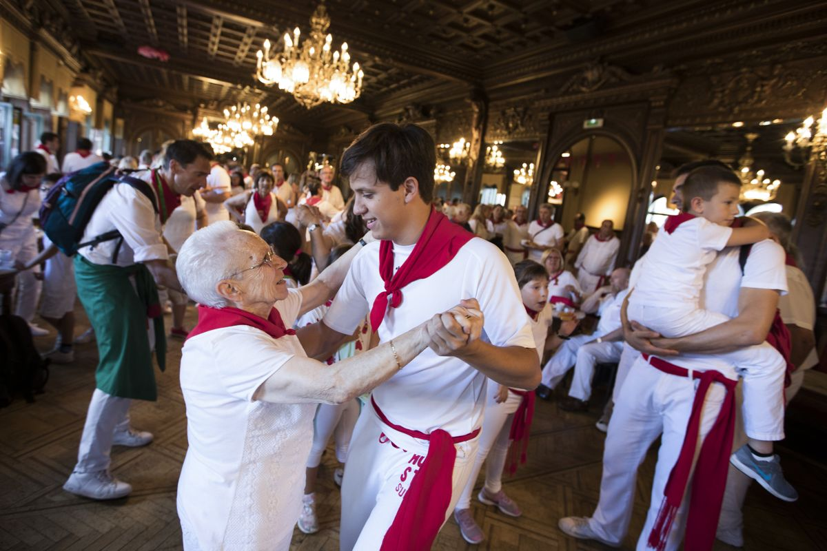 """People dance during the traditional """"Baile de la Alpargata"""" (The Espadrille Dance) during the San Fermin festival in Pamplona, northern Spain, on July 9, 2019. - People from around the world flock to the city of 200,000 residents to test their bravery and enjoy the festival's mix of round-the-clock parties, religious processions and concerts. (Photo by JAIME REINA / AFP)"""