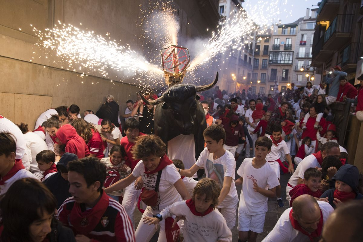 """A man wearing a costume of """"Toro de Fuego"""" (bull of fire) chases people during the San Fermin Festival on July 9, 2019, in Pamplona, northern Spain. (Photo by JAIME REINA / AFP)"""