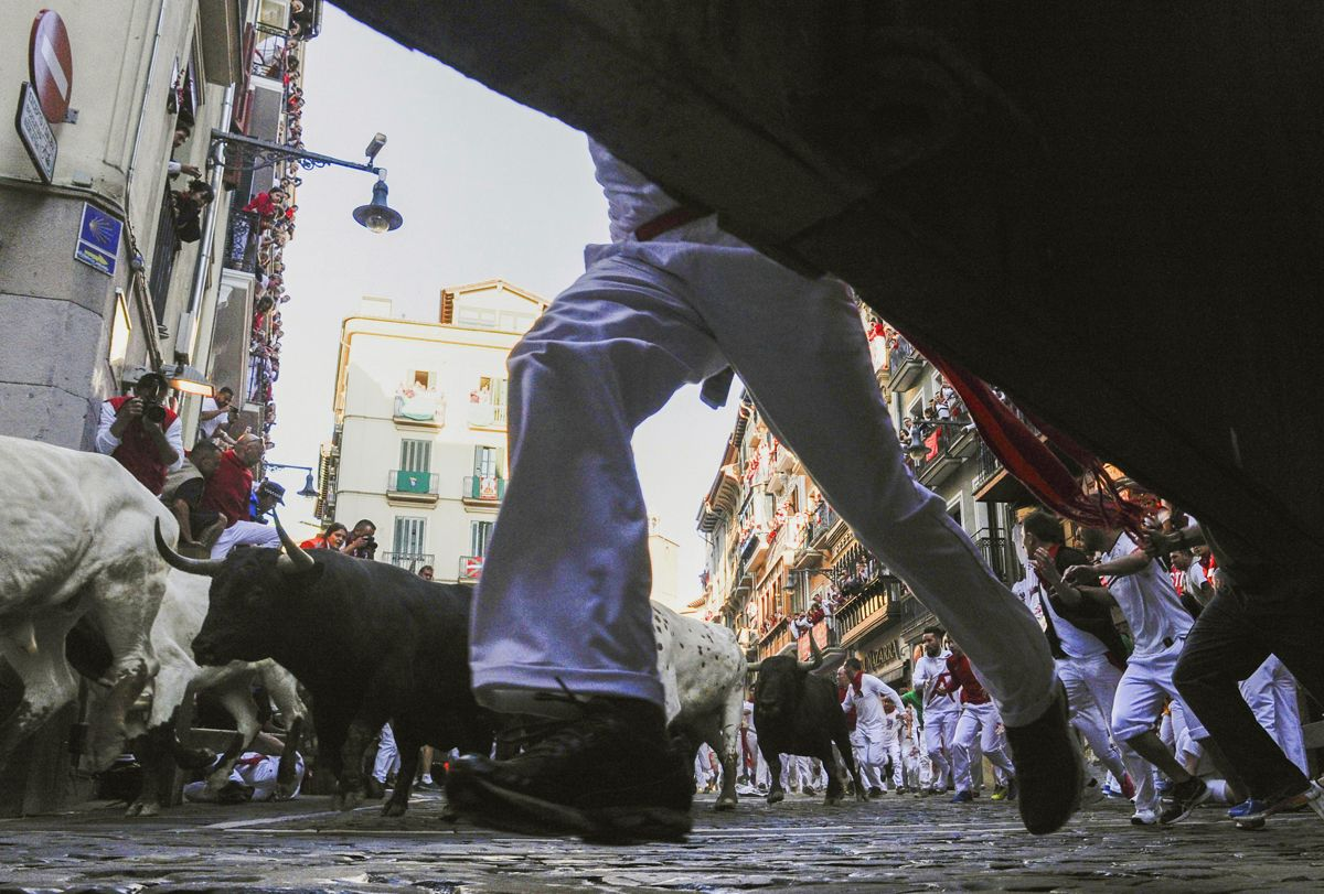 Participants run next to Jandilla fighting bulls on the fourth bullrun of the San Fermin festival in Pamplona, northern Spain on July 10, 2019. - On each day of the festival six bulls are released at 8:00 a.m. (0600 GMT) to run from their corral through the narrow, cobbled streets of the old town over an 850-meter (yard) course. Ahead of them are the runners, who try to stay close to the bulls without falling over or being gored. (Photo by ANDER GILLENEA / AFP)
