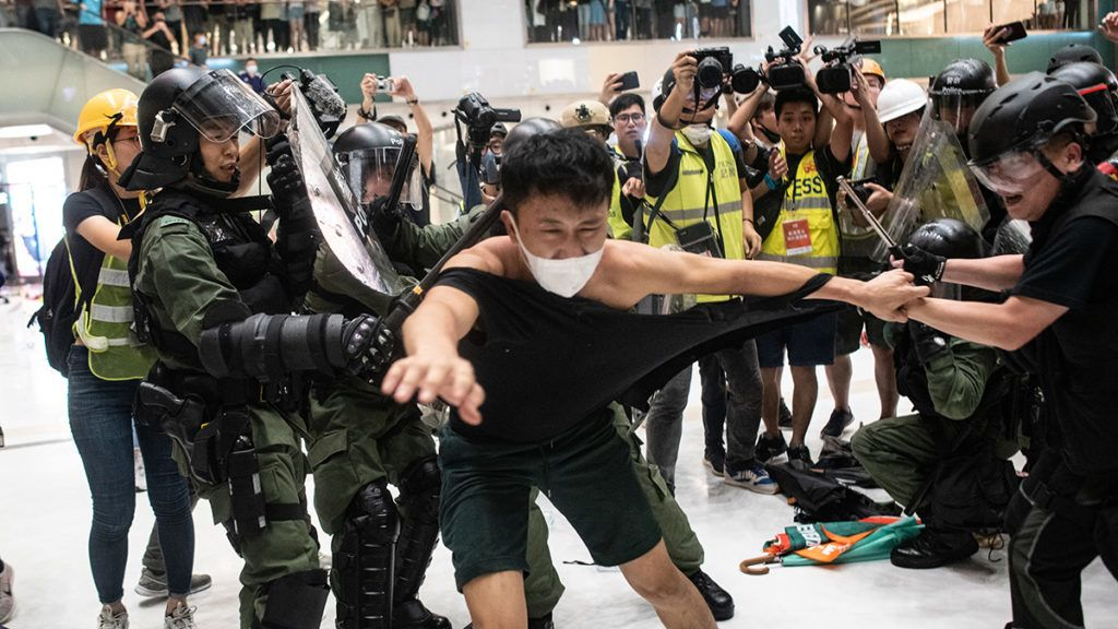 Police officers tear the shirt of a protester during a clash inside a shopping arcade in Sha Tin of Hong Kong after a rally against a controversial extradition law proposal in Sha Tin district of Hong Kong on July 14, 2019. - Riot police and protesters fought running battles in a Hong Kong shopping mall on July 14 night as unrest caused by a widely loathed plan to allow extraditions to mainland China showed no sign of abating. (Photo by Philip FONG / AFP)