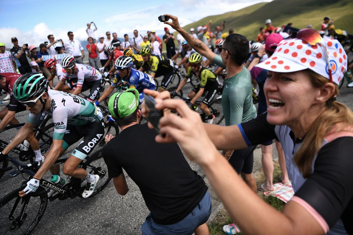 Cycling enthusiasts cheer riders in a curve uphill during the twelfth stage of the 106th edition of the Tour de France cycling race between Toulouse and Bagneres-de-Bigorre, on July 18, 2019. (Photo by JEFF PACHOUD / AFP)