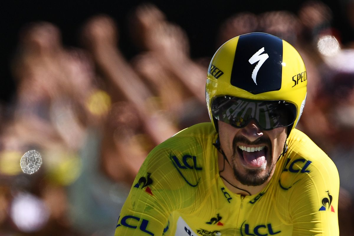 France's Julian Alaphilippe, wearing the overall leader's yellow jersey celebrates as he crosses the finish line of the thirteenth stage of the 106th edition of the Tour de France cycling race, a 27,2-kilometer individual time-trial in Pau, on July 19, 2019. (Photo by JEFF PACHOUD / AFP)