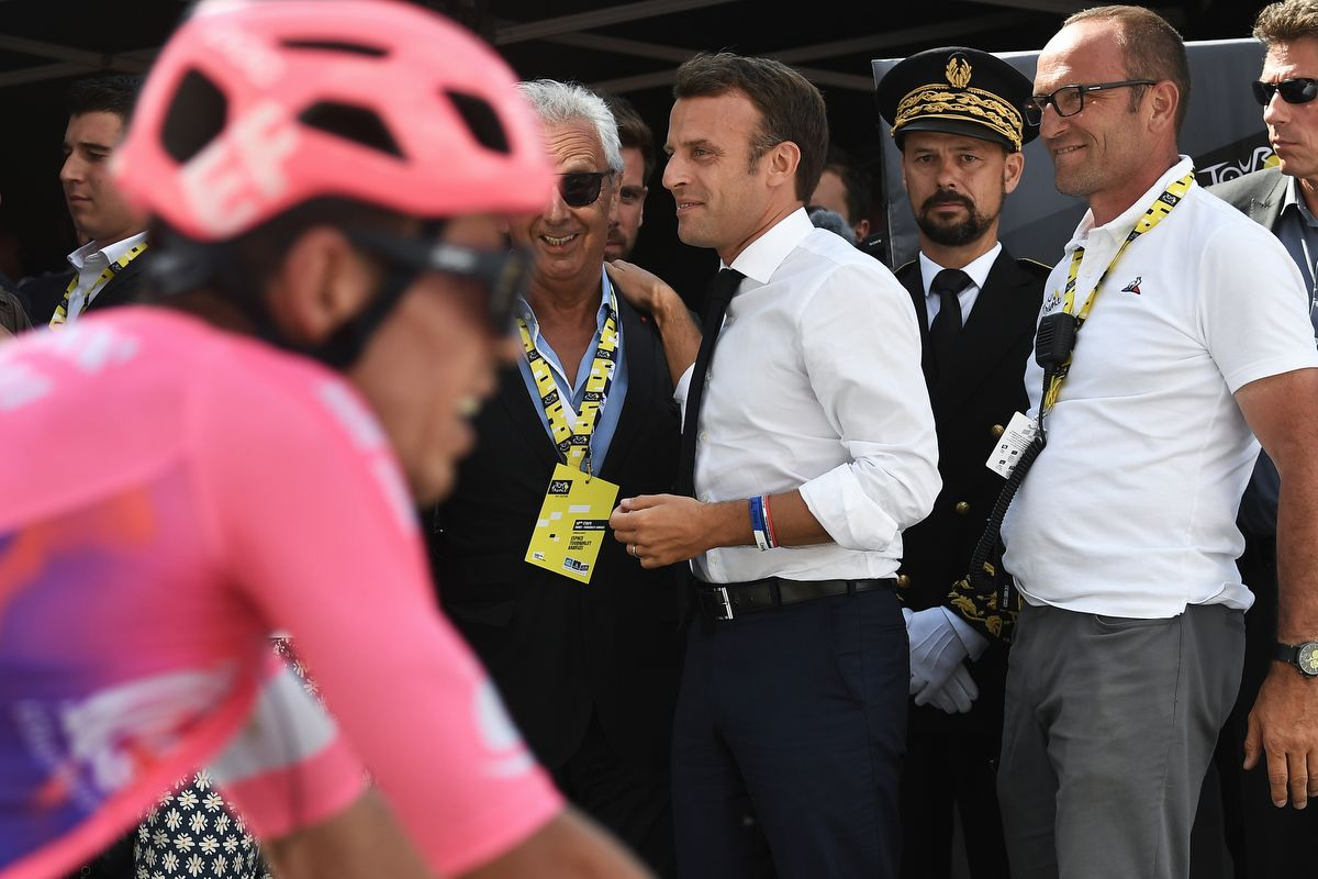 French President Emmanuel Macron (C) reacts a riders cross the finish line of the fourteenth stage of the 106th edition of the Tour de France cycling race between Tarbes and Tourmalet Bareges, in Tourmalet Bareges on July 20, 2019. (Photo by JEFF PACHOUD / POOL / AFP)