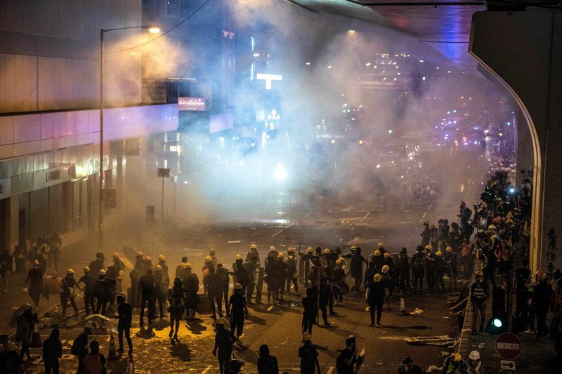 Police fire tear gas to disperse protesters after a march against a controversial extradition bill in Hong Kong on July 21, 2019. - Hong Kong descended into chaos on the night of July 21 as riot police fired multiple volleys of tear at anti-government protesters, hours after China's office in the city was daubed with eggs and graffiti in a vivid rebuke to Beijing's rule. (Photo by Laurel CHOR / AFP)