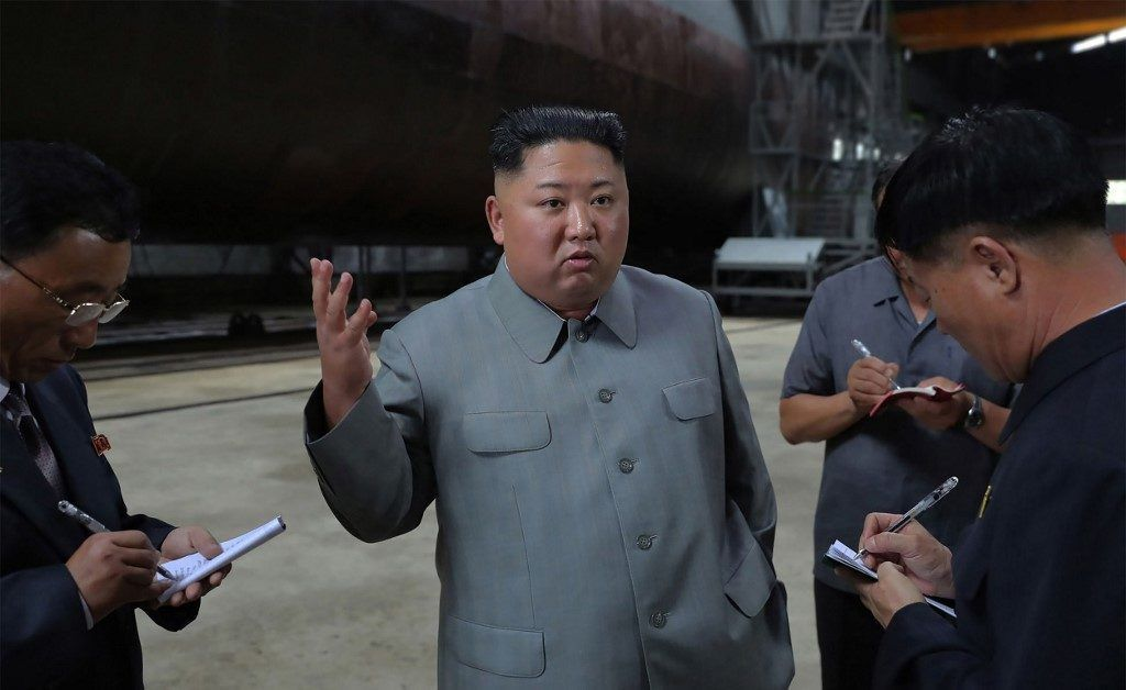 """This undated picture released from North Korea's official Korean Central News Agency (KCNA) on July 23, 2019 shows North Korean leader Kim Jong Un (C) inspecting a newly built submarine at an undisclosed location. (Photo by KCNA VIA KNS / KCNA VIA KNS / AFP) / - South Korea OUT / REPUBLIC OF KOREA OUT   ---EDITORS NOTE--- RESTRICTED TO EDITORIAL USE - MANDATORY CREDIT """"AFP PHOTO/KCNA VIA KNS"""" - NO MARKETING NO ADVERTISING CAMPAIGNS - DISTRIBUTED AS A SERVICE TO CLIENTS THIS PICTURE WAS MADE AVAILABLE BY A THIRD PARTY. AFP CAN NOT INDEPENDENTLY VERIFY THE AUTHENTICITY, LOCATION, DATE AND CONTENT OF THIS IMAGE. THIS PHOTO IS DISTRIBUTED EXACTLY AS RECEIVED BY AFP. /"""