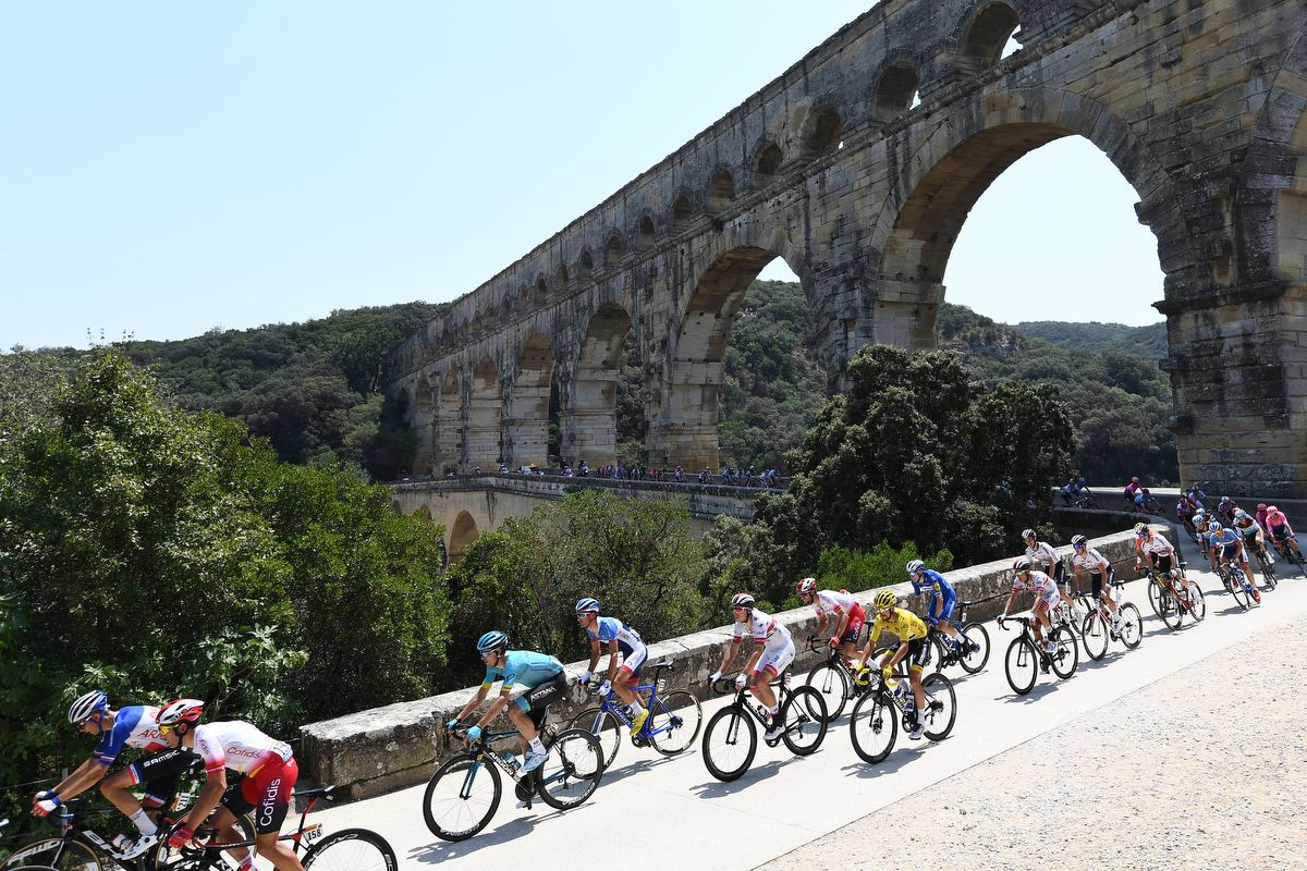 France's Julian Alaphilippe (frontC), wearing the overall leader's yellow jersey and cyclists cross the Pont du Gard during the sixteenth stage of the 106th edition of the Tour de France cycling race between Nimes and Nimes, in Nimes, on July 23, 2019. (Photo by Anne-Christine POUJOULAT / AFP)