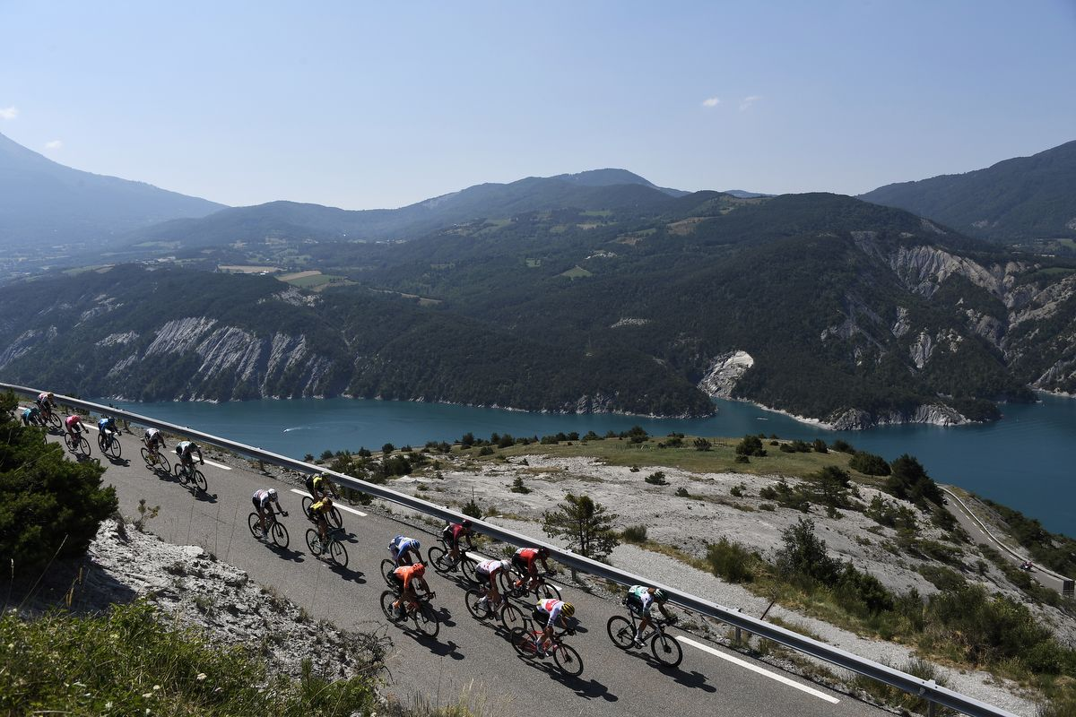 Cyclists of the pack ride past the Lac of Serre-Poncon (Serre-Poncon lake) during the eighteenth stage of the 106th edition of the Tour de France cycling race between Embrun and Valloire, in Valloire, on July 25, 2019. (Photo by JEFF PACHOUD / AFP)