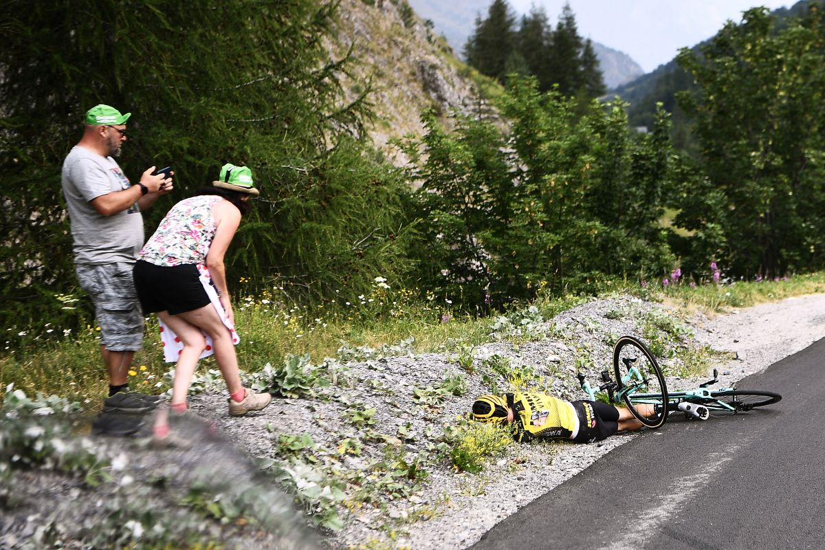 Fans look at New Zealand's George Bennett after a fall during the eighteenth stage of the 106th edition of the Tour de France cycling race between Embrun and Valloire, in Valloire, on July 25, 2019. (Photo by Anne-Christine POUJOULAT / AFP)