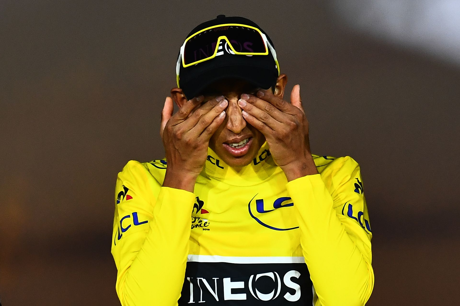 Colombia's Egan Bernal wipes his eyes celebrates his overall leader's yellow jersey on the podium of the 21st and last stage of the 106th edition of the Tour de France cycling race between Rambouillet and Paris Champs-Elysees, in Paris on July 28, 2019. (Photo by Marco Bertorello / AFP)