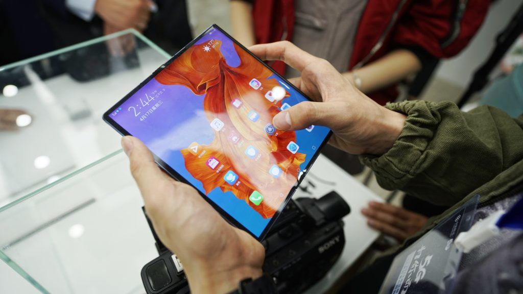 A Chinese employee shows 5G wireless network on a Huawei Mate X, the first 5G foldable smartphone of Huawei, at the first experience area featuring 5G wireless network in Hangzhou city, east China's Zhejiang province, 17 April 2019.  The first experience area featuring 5G wireless network opened to the public in Hangzhou, Zhejiang province, on April 5, offering locals a glimpse at the next-generation technology. The area aims to provide a taste of what's in store with 5G network, featuring autonomous vehicles, virtual reality and a robot that claims to be unbeatable at rock-paper-scissors – thanks to an artificial intelligence algorithm and 5G technologies which allow it to predict its opponent's move based on hand gestures. With a higher speed and lower latency, 5G network has a peak download speed of 2.8 Gbps, about 10 times that of 4G.