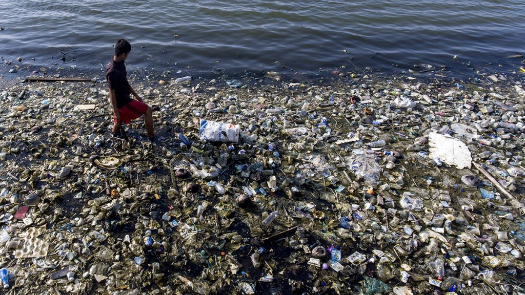 This picture taken by a drone, a child is in a reservoir area of contaminated with garbage to look for used plastic in Lhokseumawe, Aceh, Indonesia on Friday June 28, 2019. Much of that ends up in landfill or in the seas. Based on a study released by McKinsey and Co. and Ocean Conservancy, Indonesia us the number two plastic waste producer in the world after China.  (Photo by Zick Maulana/NurPhoto)