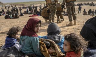 """Civilians evacuated from the Islamic State (IS) group's embattled holdout of Baghouz wait at a screening area held by the US-backed Kurdish-led Syrian Democratic Forces (SDF), in the eastern Syrian province of Deir Ezzor, on March 5, 2019. - Kurdish-led forces launched a final assault Friday on the last pocket held by the Islamic State group in eastern Syria, their spokesman said. The """"operation to clear the last remaining pocket of ISIS has just started"""", Mustefa Bali, the spokesman of the US-backed Syrian Democratic Forces, said in a statement using an acronym for the jihadist group. (Photo by Bulent KILIC / AFP)"""