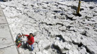 A man with a bike walks on hail in the eastern area of Guadalajara, Jalisco state, Mexico, on June 30, 2019. - The accumulation of hail in the streets of Guadalajara buried vehicles and damaged homes. (Photo by ULISES RUIZ / AFP)