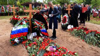 """People mourn after a funeral ceremony at a cemetery in Saint Petersburg on July 6, 2019, three days after a fire that killed 14 officers on what was reportedly a nuclear-powered mini-submarine. - The fire on a Russian submersible that killed 14 navy officers this week started in the vessel's battery compartment and did not impact its nuclear reactor. According to Russian medias, the submarine is a Russian AS-31, a nuclear-powered deep-water submarine that is part of the """"Losharik"""" project, the unofficial name for a project run by the top-secret Main Directorate of Deep Sea Research (GUGI). (Photo by OLGA MALTSEVA / AFP)"""