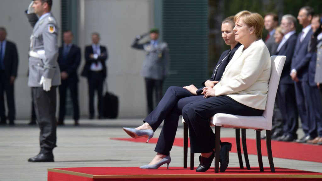 German Chancellor Angela Merkel (R) and Denmark's Prime Minister Mette Frederiksen sit as they listen to the national anthems during a welcoming ceremony with military honours on July 11, 2019 in the courtyard of the Chancellery in Berlin. - German Chancellor Angela Merkel had suffered her third trembling spell in less than a month the day before, on July 10, 2019. It had focused attention on her health, after she began shaking involuntarily as national anthems were being played at the reception of the Finnish Prime Minister. (Photo by Tobias SCHWARZ / AFP)