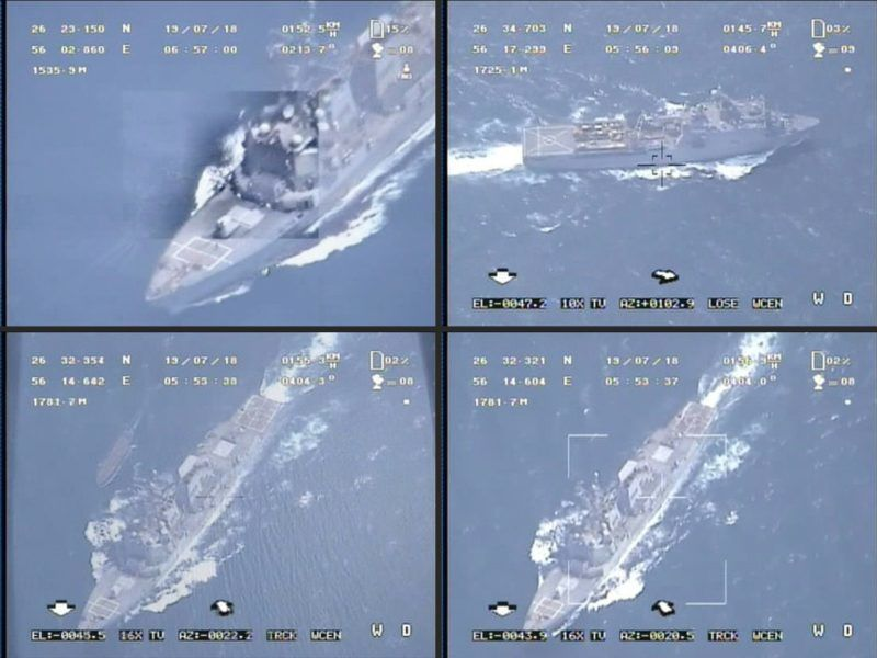 """(COMBO) This combination of image grabs created from a video broadcast by Iran's Islamic Revolutionary Guard Corps (IRGC) on July 19, 2019 reportedly shows footage obtained from an IRGC drone flying above a warship at an undisclosed location. - Iran's Revolutionary Guards released a video on July 19 claiming it belies the claim that the Boxer had downed an Iranian drone. The footage seems to be shot from a high altitude and shows a convoy of ships passing through, and according to the IRGC shows """"tracking (of) the helicopter-carrier (Boxer) LHD-4 in the Strait of Hormuz"""". (Photos by - / Iran's Islamic Revolutionary Guard Corps (IRGC) / AFP)"""