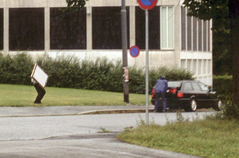 """Armed robbers flee the scene after robbing the Munch Museum in Oslo and load the paintings into the back of a getaway car, 22 August 2004 at around 11am local time. The armed thieves stormed in as the museum was about to open to the public and made away with, among others, Edvard Munch's best known paintings """"The Scream"""" and """"Madonna"""". (Photo by POLICE / SCANPIX / AFP)"""