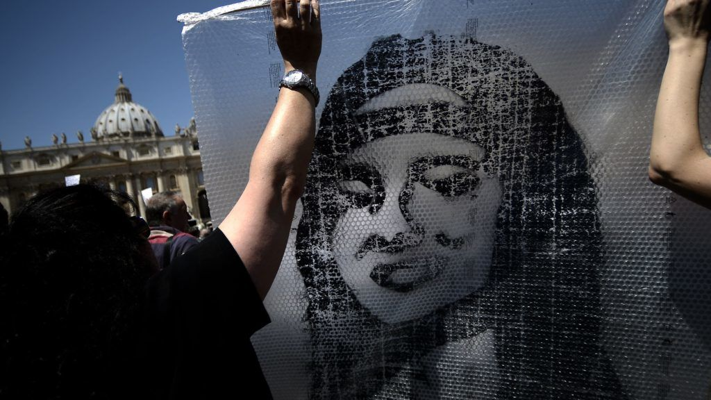 """A demonstrator holds a poster of Emanuela Orlandi reading """"Missing"""" during Pope Benedict XVI's Regina Coeli noon prayer in St. Peter's square, at the Vatican on May 27, 2012. Fifteen-year-old Emanuela Orlandi, the daughter of a Vatican messenger who lived with his family in Vatican City, disappeared 25 years ago (June 22, 1983) when she went to a music lesson..   AFP PHOTO/ FILIPPO MONTEFORTE (Photo by FILIPPO MONTEFORTE / AFP)"""