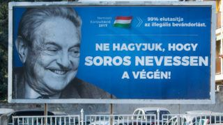 """A poster with US billionaire George Soros is pictured on July 6, 2017 in Szekesfehervar, Hungary. - The head of Hungary's largest Jewish organisation says a """"poisonous"""" poster campaign by the government that targets US billionaire George Soros is stoking anti-Semitic sentiments and urged its immediate scrapping. (Photo by ATTILA KISBENEDEK / AFP) / TO GO WITH AFP STORY"""