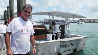 Cuban exile organization Movimiento Democracia president Ramon Saul Sanchez prepares one of the boats of the flotilla to commemorate the drowning of 37 migrants twenty years ago, on July 12, 2014 in Key West, Florida. Three boats carrying 25 people launched fireworks on Saturday evening in international waters some 12 nautical miles from the Cuban capital Havana.     AFP PHOTO/Diego URDANETA (Photo by Diego URDANETA / AFP)