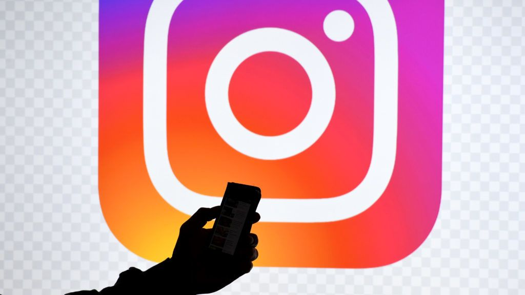 15 March 2019, Schleswig-Holstein, Aukrug-Homfeld: ILLUSTRATION - A smartphone in front of a monitor with the logo of the provider Instagram. Photo: Carsten Rehder/dpa