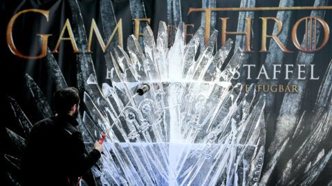 """16 April 2019, Berlin: A young man is working on a throne of ice. At the start of the final season of the fantasy saga """"Game of Thrones"""" the fans can climb the ice throne. Photo: Britta Pedersen/dpa"""