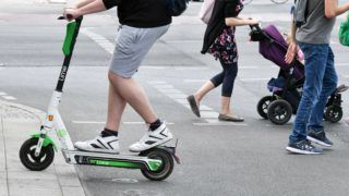 05 July 2019, Berlin: An electric pedal scooter and pedestrian in traffic. E-scooters may be used in Germany since mid-June. Photo: Jens Kalaene/dpa-Zentralbild/ZB