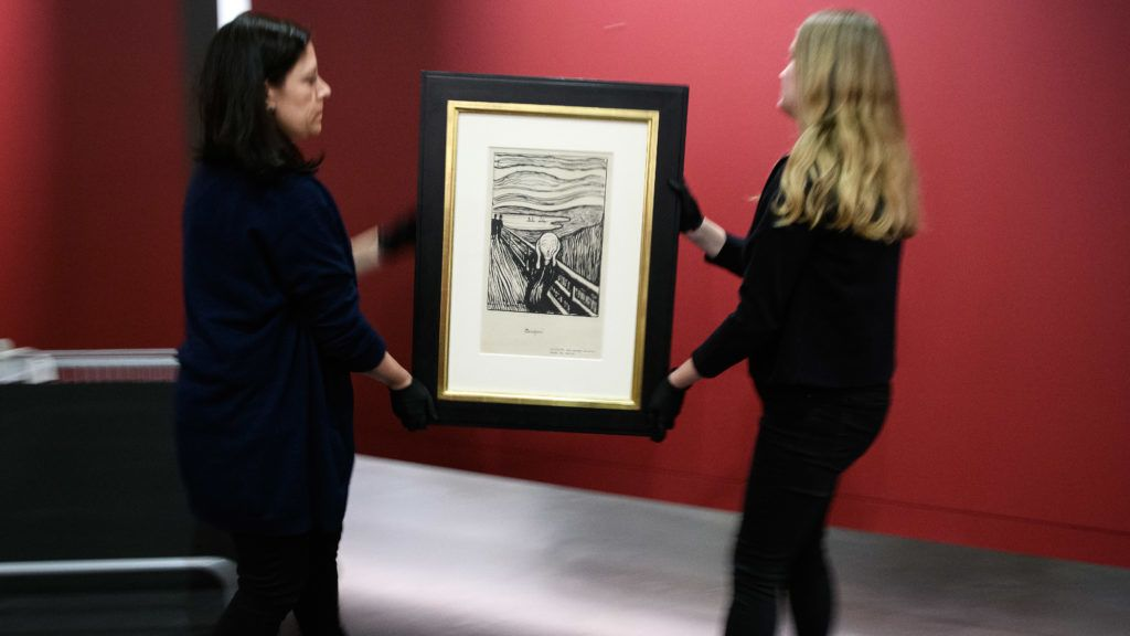 """LONDON, ENGLAND - MARCH 20: Gallery assistants prepare to hang a lithograph print of """"The Scream"""" by Edvard Munch during a press event to promote the """"Edvard Munch: love and angst"""" exhibition on March 20, 2019 in London, England. The print is one of around 15 lithographs made by Munch and was made before the famous colour painting. The exhibition runs from April 11 to July 21 2019 and is the largest UK exhibition of his work in 45 years. (Photo by Leon Neal/Getty Images)"""
