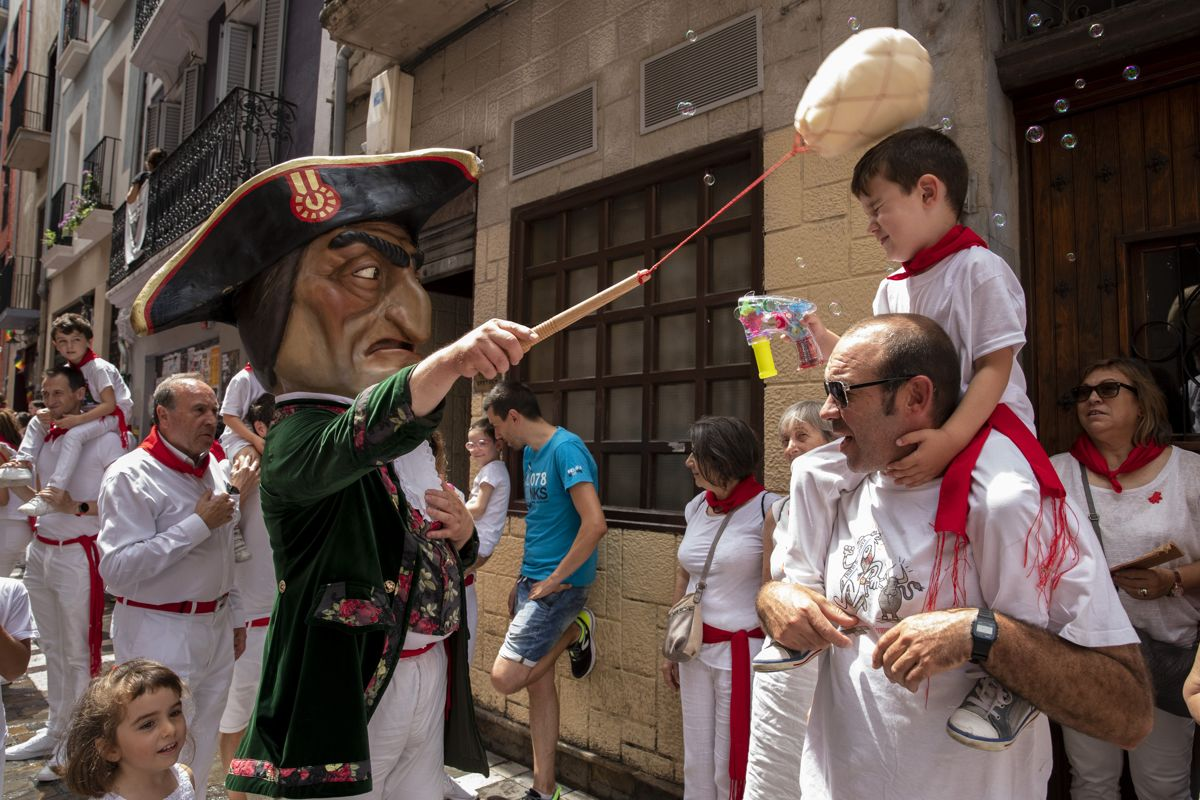 PAMPLONA, SPAIN - JULY 08: Caravinagre 'Vinegar face' kiliki hits with a sponge to a boy during the Comparsa de Gigantes y Cabezudos, or Giants and Big Heads parade on the third day of the San Fermin Running of the Bulls festival on July 08, 2019 in Pamplona, Spain. The annual Fiesta de San Fermin, made famous by the 1926 novel of US writer Ernest Hemmingway entitled 'The Sun Also Rises', involves the daily running of the bulls through the historic heart of Pamplona to the bull ring. (Photo by Pablo Blazquez Dominguez/Getty Images)