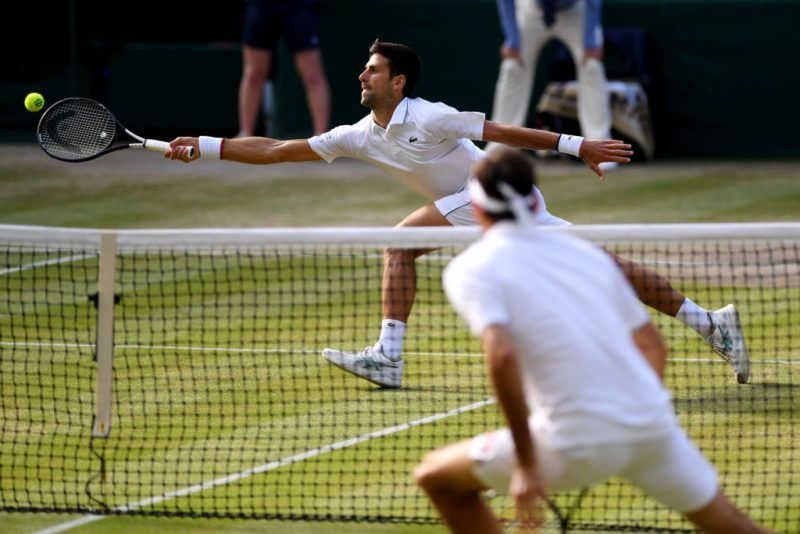 LONDON, ENGLAND - JULY 14: Novak Djokovic of Serbia stretches to play a forehand in his Men's Singles final against Roger Federer of Switzerland during Day thirteen of The Championships - Wimbledon 2019 at All England Lawn Tennis and Croquet Club on July 14, 2019 in London, England. (Photo by Matthias Hangst/Getty Images)