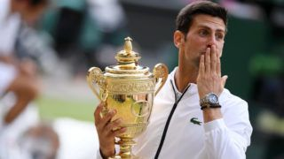 LONDON, ENGLAND - JULY 14: Novak Djokovic of Serbia celebrates with the trophy after winning his Men's Singles final against Roger Federer of Switzerland during Day thirteen of The Championships - Wimbledon 2019 at All England Lawn Tennis and Croquet Club on July 14, 2019 in London, England. (Photo by Matthias Hangst/Getty Images)