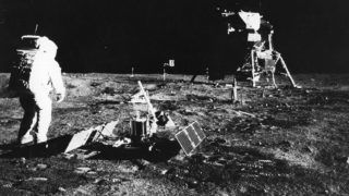 1969:  Apollo 11 astronaut Edwin 'Buzz' Aldrin deploys a scientific experiment package on the surface of the moon.  In the background is the Lunar Module, as is a flag of the United States.  (Photo by Neil Armstrong/NASA/Getty Images)