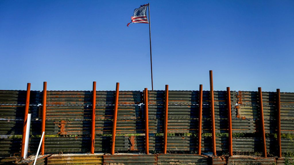 A tattered flag flies along the U.S.-Mexico border wall in Campo, CA on Wednesday, May 11, 2011. (Photo by Sandy Huffaker/Corbis via Getty Images)