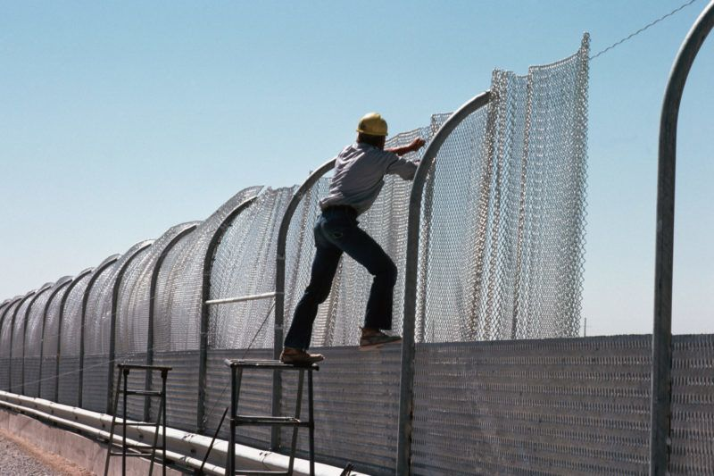 """A construction worker pulls steel mesh into place on a section of the galvanized steel fence being built along the border between the United States and Mexico in 1979. The fence, intended to keep illegal aliens from crossing into the US, is known as the """"Tortilla Curtain."""" (Photo by © Stephanie Maze/CORBIS/Corbis via Getty Images)"""