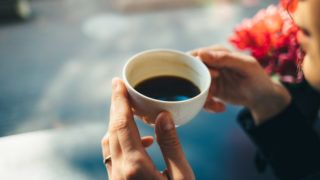 Cup of coffee in woman's hands, close-up. Girl drinking espresso at table near window in cafe on sunny morning.