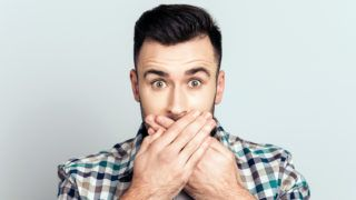 Oops! Close up portrait of attractive man closed his mouth with crossed hands and wide opened eyes, looking at camera, he can't believe his eyes, standing over grey background
