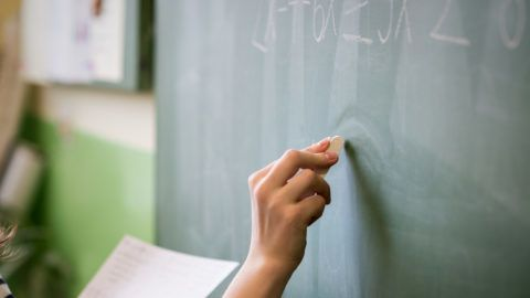 Young female teacher or a student writing math formula on blackboard in classroom.