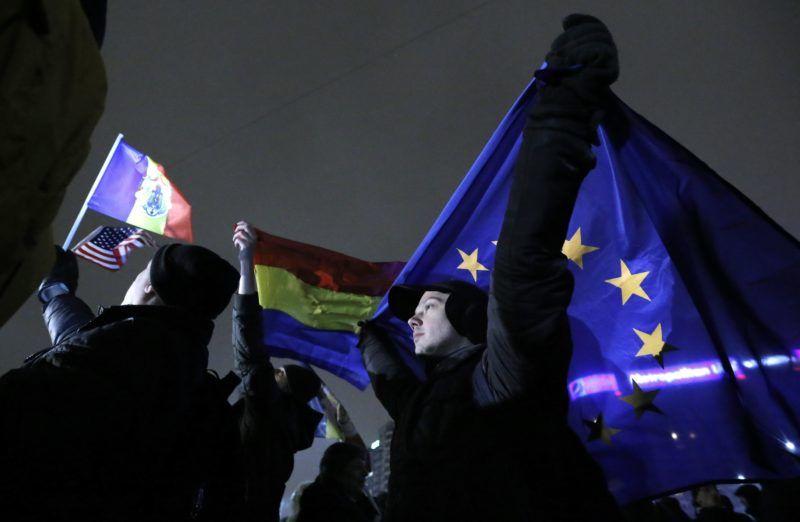 Bukarest, 2018. február 22. Román és EU-zászlót tartanak demonstrálók a bukaresti kormánypalota elõtti téren 2018. február 22-én este, miután Tudorel Toader igazságügyi miniszter bejelentette, hogy kezdeményezi Laura Codruta Kövesi, a román korrupcióellenes ügyészség (DNA) vezetõjének elmozdítását. A tüntetõk a korrupcióellenes harc folytatását, az igazságügyi miniszter és az egész kormány lemondását követelték. Klaus Iohannis román államfõ védelmébe vette Laura Codruta Kövesit. (MTI/EPA/Robert Ghement)
