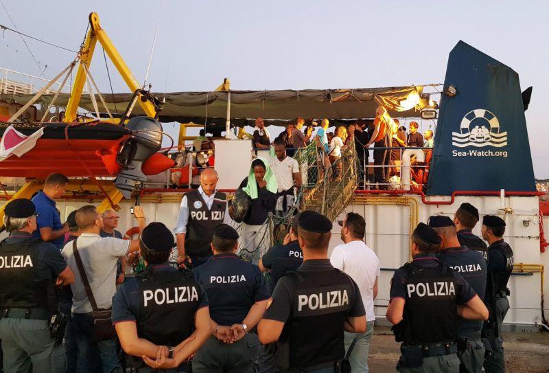 Lampedusa, 2019. június 29. Európába igyekvõ illegális bevándorlók rendõri õrizet mellett partra szállnak Lampedusán 2019. június 29-én, miután az õket szállító Sea Watch 3, a Sea-Watch nevû német nem kormányzati szerv holland bejegyzésû hajója kikötési engedély nélkül, erõszakkal behajtott a kikötõbe. Az olasz hatóságok hajói megpróbálták feltartóztatni, de a Sea Watch 3 az egyiknek majdnem nekiment és a dokknak szorította. A kapitányt õrizetbe vették. MTI/EPA/ANSA/Elio Desiderio
