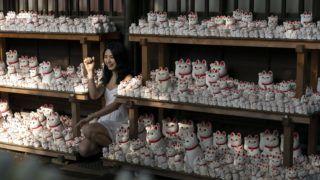 Tokió, 2019. július 9. A 2019. június 25-i képen integetõ macskákat ábrázoló szobrok közt fényképezkedik egy nõ a Gótoku-dzsi buddhista szentély kertjében, Tokió Szetagaja nevû városrészében. Valószínûleg innen terjedt el a szigetországban, sõt Kínában is egyre népszerûbb, gyakran mechanikus karlendítést végzõ és több színváltozatban készülõ integetõ macska, amelytõl sokan szerencsét és jólétet remélnek, és elõszeretettel állítják ki irodákban, üzlethelyiségekben vagy otthonukban. MTI/AP/Jae C. Hong